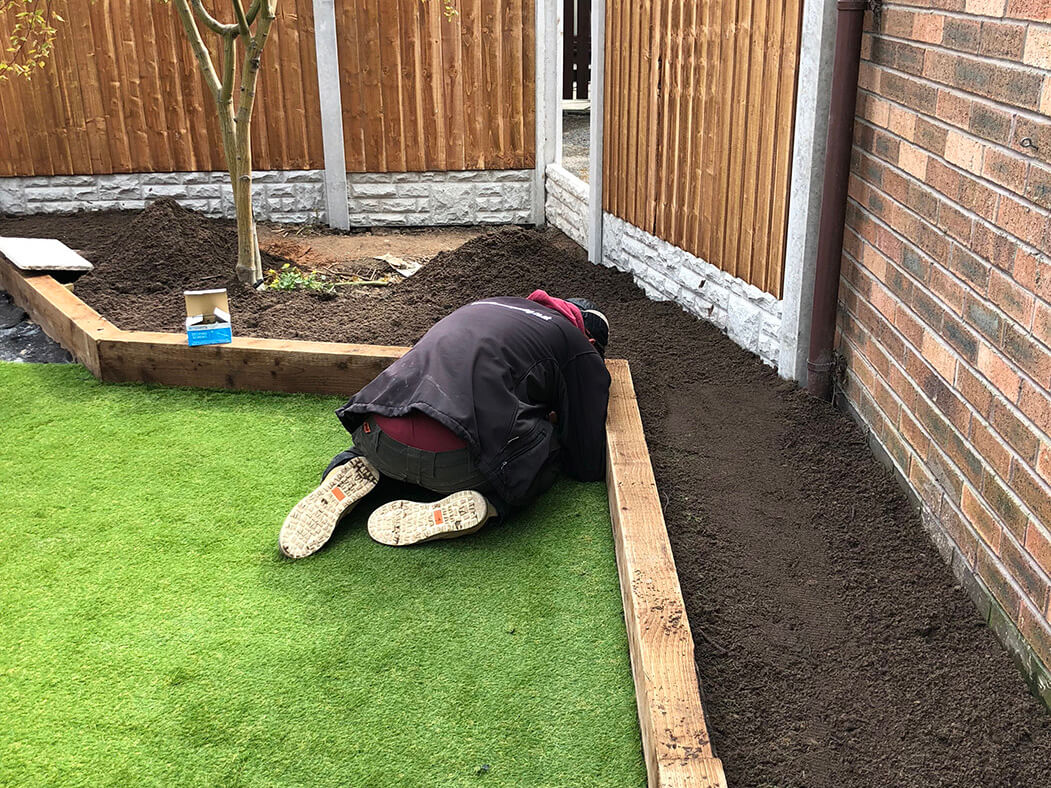 contractor completing artificial lawn and landscaping in lancashire