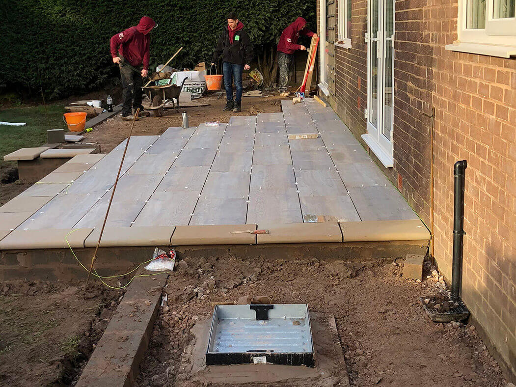 workers completing porcelain patio teak wood effect in morecambe