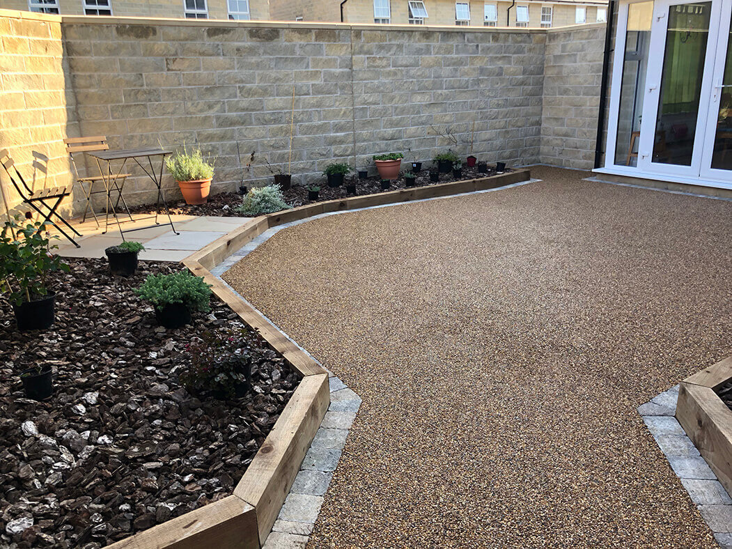 View of Resin Bound patio installed in Lancashire, near Lancaster showing raised flower beds and seating area.
