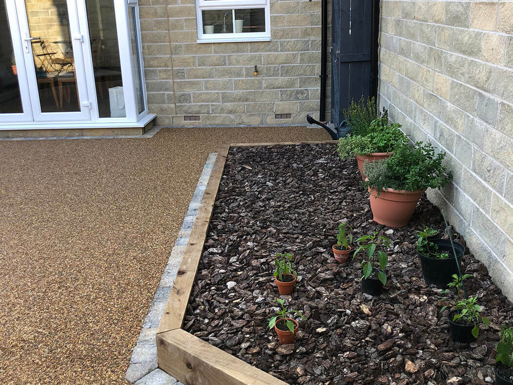 View of Resin Bound patio installed in Morecambe with raised flower bed.